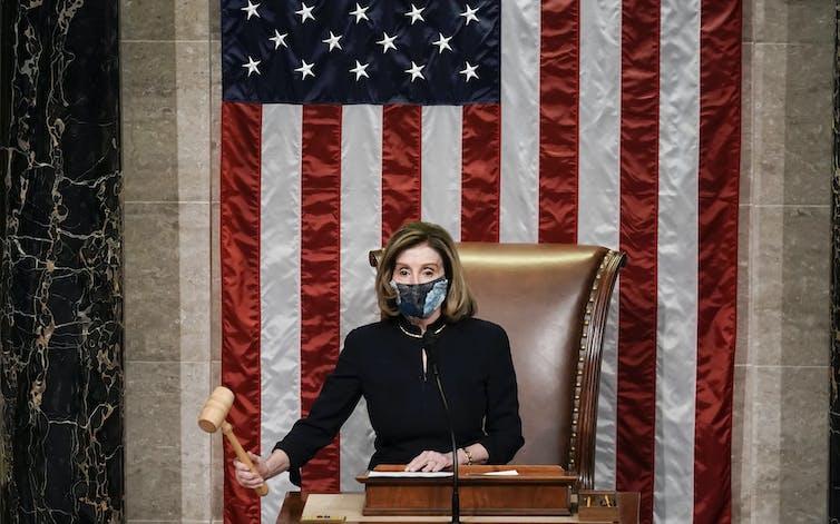 Nancy Pelosi, in a mask, lowers the gavel.