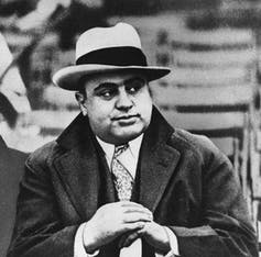 Al Capone in a fedora and a coat and tie.