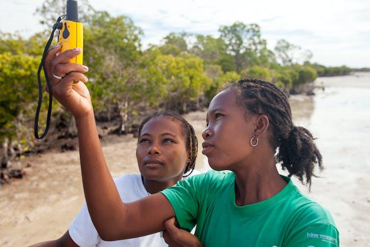 Dua perempuan memegang GPS dekat pohon bakau.
