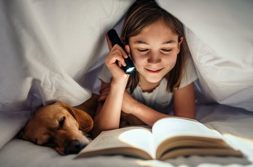 A girl reads a book under her bed covers late at night.