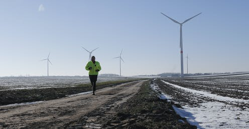 A jogger passes snow-covered fields with wind turbines in the background.