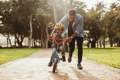 Picture of a man teaching his child to ride a bike.