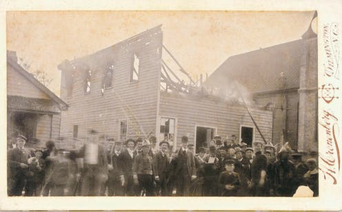 An armed mob of white insurrections in front of the Black newspaper building they burned.
