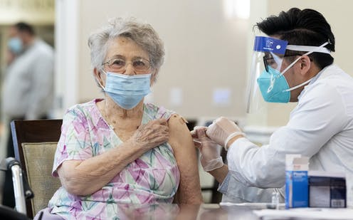 A woman is vaccinated in a nursing home.