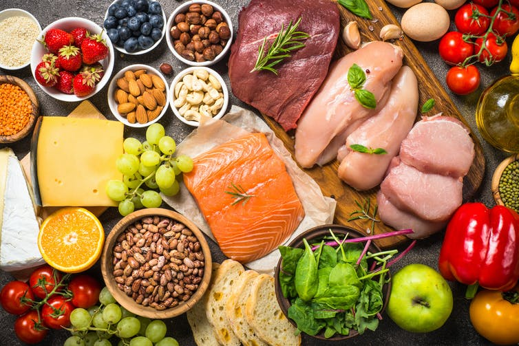 An assortment of healthy foods, including salmon, berries, cheese, and legumes.