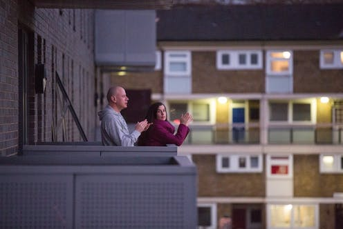 A couple clap for the NHS from their flat balcony.