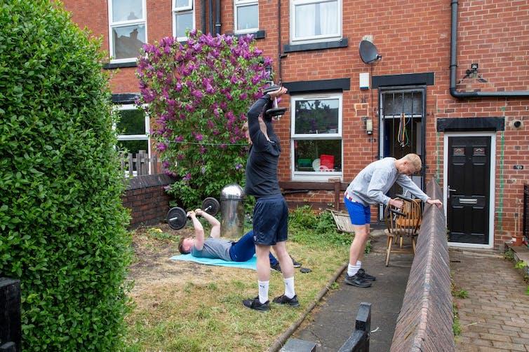 Three men work out in their garden 'gym' during lockdown.