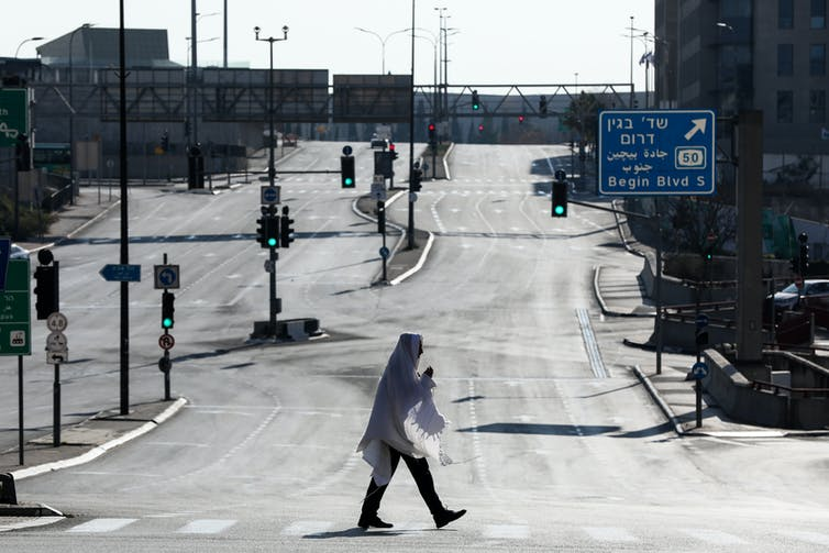 View of empty roads with solitary person walking.