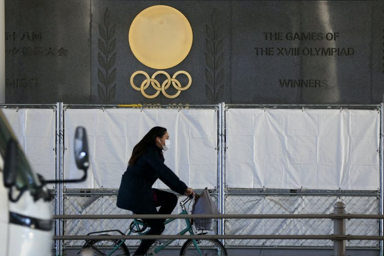 A woman wearing a face mask riding a bicycle past an Olympics logo
