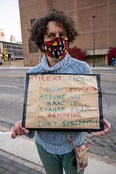 Woman wearing a mask holds a sign likening COVID-19 to racism – 'assume you have it'