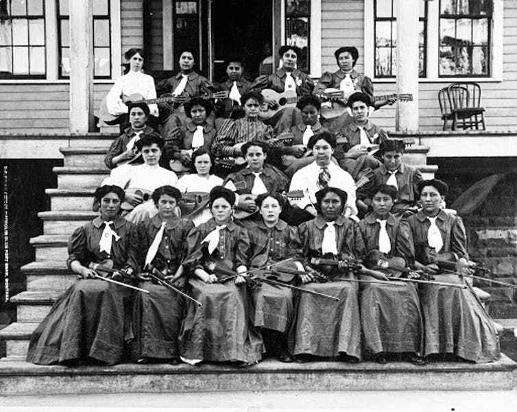 Black-and-white image of Native students in Victorian dresses holding violins