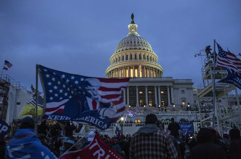 Evening shot of the capitol lit up with flag-flying protesters in foreground
