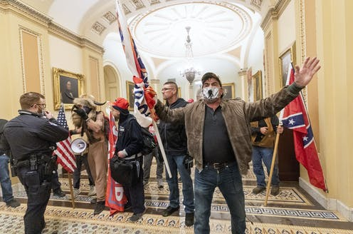 Rioters carrying white supremacist symbols inside the Capitol
