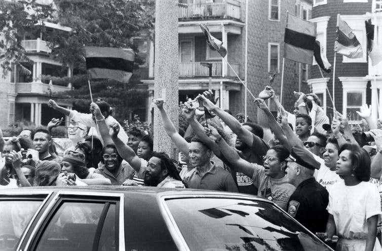 Black-and-white image of Black people cheering for Nelson Mandela.