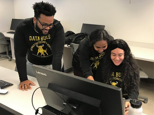 """Three college students wearing sweat shirts that say """"DATA BULLS"""" are at a computer."""