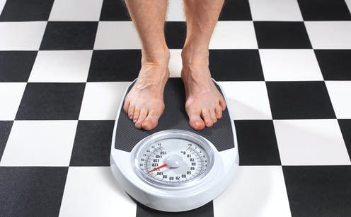 A man stands on a bathroom scale.