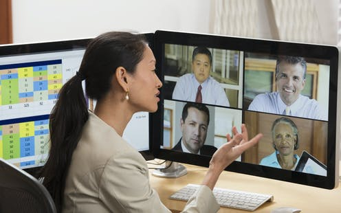 A woman holds up her hand as she talks to four people using video conferencing software.