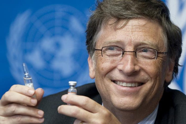 Bill Gates in front of UN logo holding a vaccine.