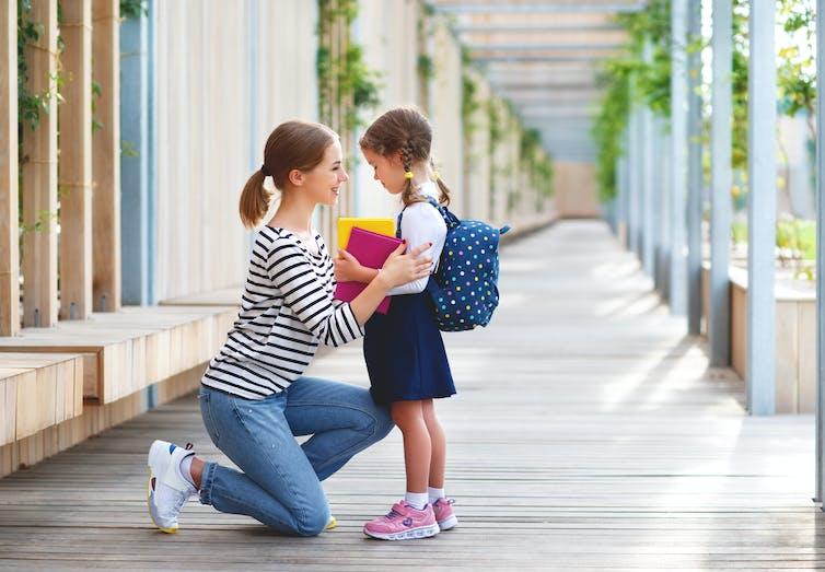 Mother talking to her schoolgirl kid and smiling in the school corridor.