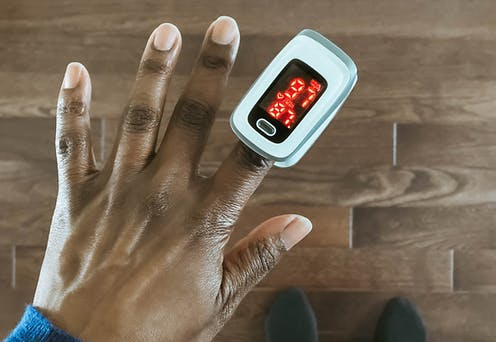 A woman uses a pulse oximeter.