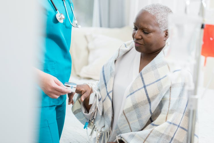 A nurse monitors a woman using a pulse oximeter.
