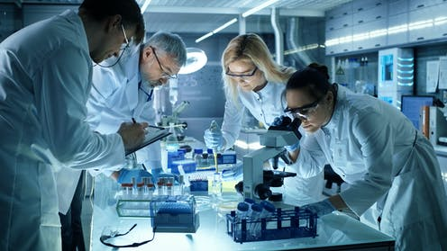 Team of four scientists in lab researching