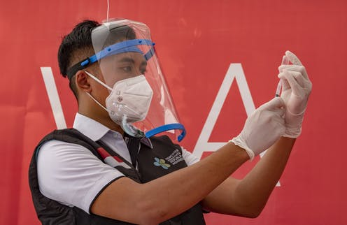 A medical worker in Indonesia loading a syringe with vaccine fluid