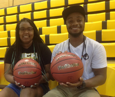 Two African American students each hold a basketball as they sit down on a bench.