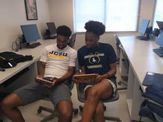 Two African American students use iPads in a computer room.