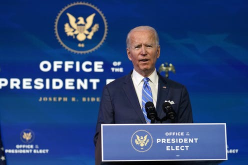 Joe Biden in a blue suit and tie speaks behind a podium that says Office of the President Elect.