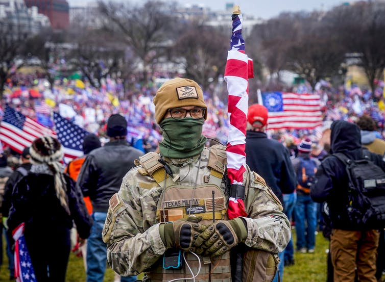Glasses-wearing man in military fatigues poses with an American flag in front of a large crowd