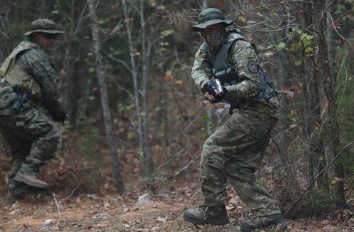 Men in military fatigues run with weapons in the woods