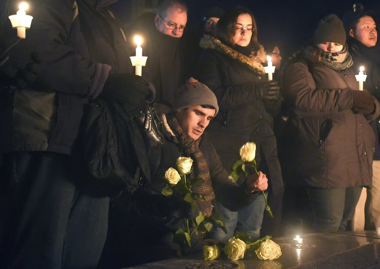 A man places roses by the Centennial Flame during a vigil on Parliament Hill. Others stand behind him holding candles.