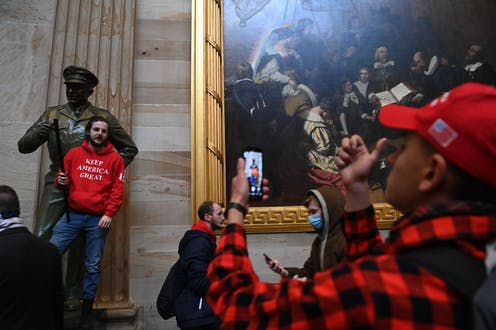 A man uses a cell phone to take a photo of another man standing on the pedestal of a statue in the U.S. Capitol building.