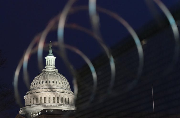 The U.S. Capitol dome is seen in the darkness behind razor wire.