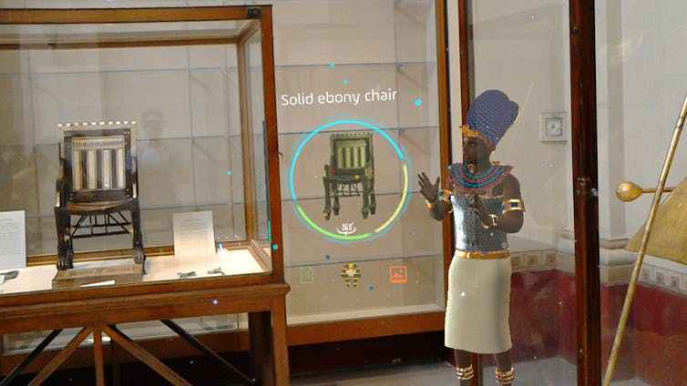 An animated pharoh shows off an ancient chair in a museum
