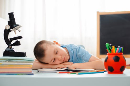 Boy sleeping at the desk with microscope and learning materials around him.
