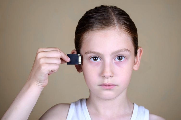 A girl inserting memory chip into her brain.