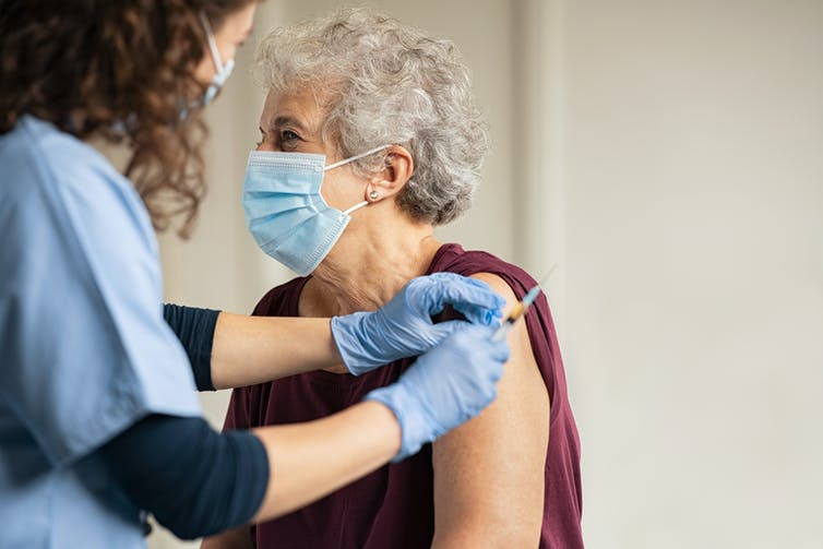 A nurse administers a vaccine to an elderly lady wearing a mask.