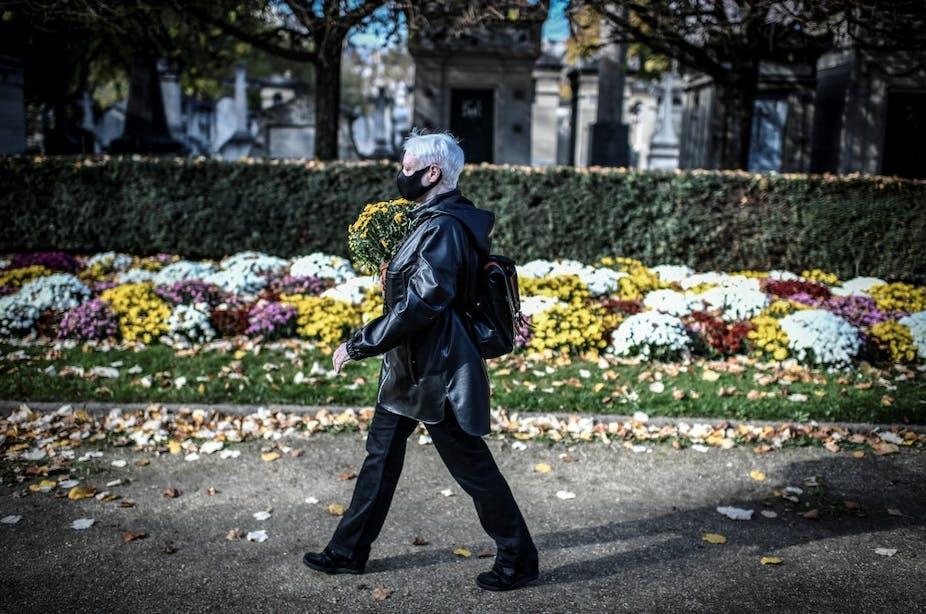 Une femme portant un masque apporte des fleurs au cimetière Montparnasse