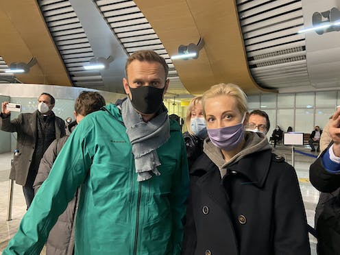Middle-aged man and woman posing in COVID masks for a photograph at Moscow's Sheremetyevo airport.
