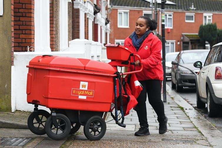 Royal Mail woman postie pushing trolley full of post on her rounds during lockdown.