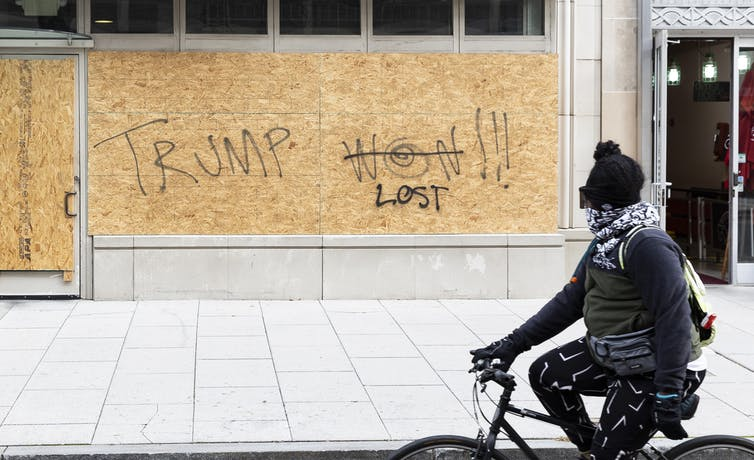 A cyclist looking at graffiti that originally said 'Trump won!' but has been changed to read 'Trump lost'.