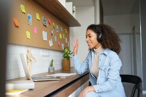Woman smiling and waving at computer screen