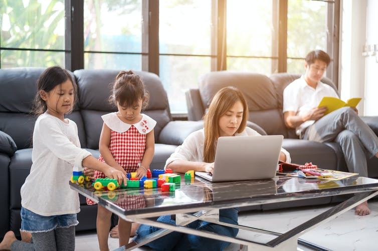 Family scene with two daughters playing, mother working on laptop, father reading