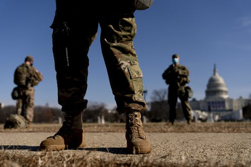 National Guard soldiers are seen with the U.S. Capitol in the background on a sunny day.