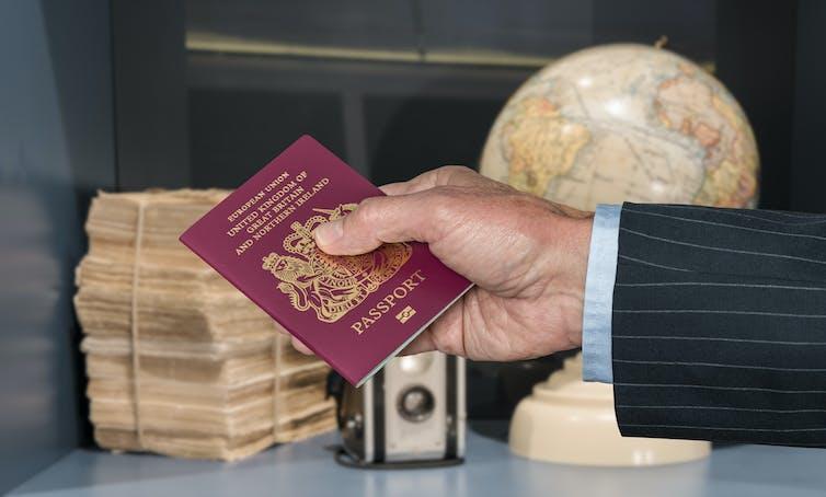 Senior executive hand holding UK passport against blurred background of world globe and camera