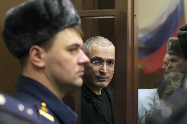 Russian security officers watch a bespectacled man in a Moscow courtroom.