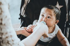 A baby looks at his mother while sucking on his bottle in a stroller.