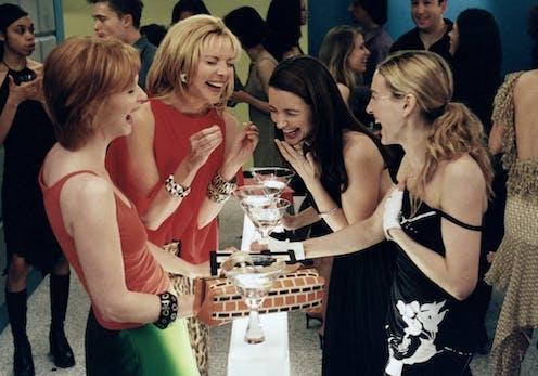 Four women at bar laughing.